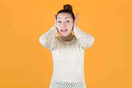 the girl covers her ears with her hands, not wanting to listen to anything, looks at the camera. Isolated on orange-yellow