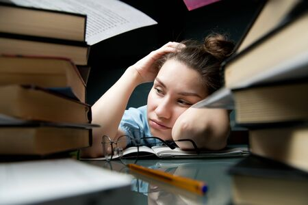 The young woman is tired of studying and bored sleepily at the table, falls asleep Stock fotó