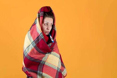 the sick girl wrapped herself in a checkered plaid and holds a thermometer in her mouth, looks away. Isolated on an orange-yellow background.