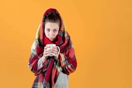 A sickly-looking girl wrapped herself in a warm plaid and looks tiredly forward with a mug of tea in her hands. Isolated on an orange-yellow background. Stock fotó