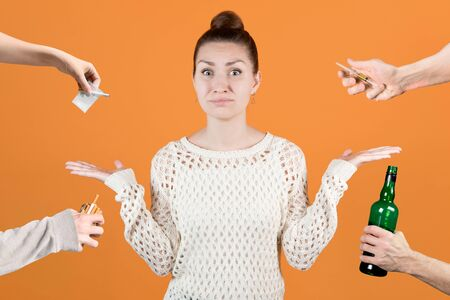 girl is indignant at the fact that from all sides harmful substances are offered to her - drugs, alcohol, smoking. Isolated on an orange background. Bad environment, bad company, doubtful friends Stock fotó