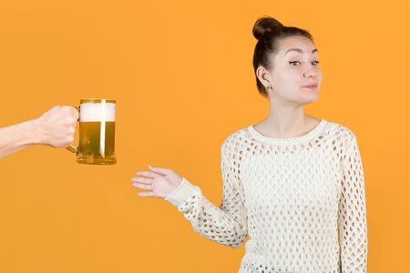 The girl with undisguised joy agrees to take a mug of fresh beer from the hands of a man. Isolated on a yellow background. Beer alcoholism, female alcoholism. Youth and alcohol