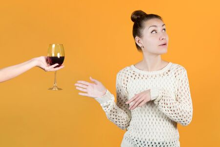 The girl looks away, but happily takes a glass of red wine. Isolated on a yellow background. Female alcoholism, love of wine