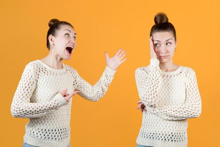 Split personality. The girl chastises herself and resists this herself. Both women - one and the same face, montage on an orange background