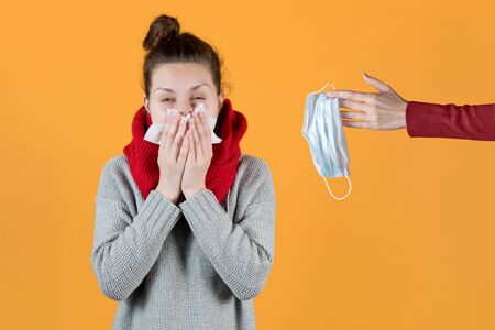 A girl with symptoms of the virus and a cold is offered to wear a mask. A hand holds out a medical mask to a girl who is actively sneezing and coughing. Isolated on orange background.