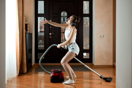 Young woman having fun while vacuuming, singing and listening to music on headphones