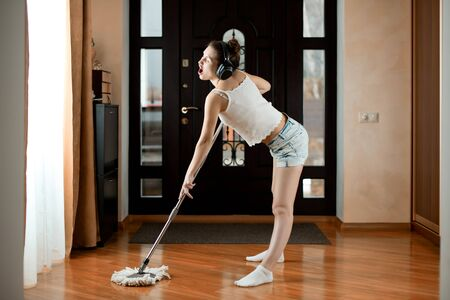 Cheerful house cleaning girl in headphones with music and mopping floors. Funny cleaning Stock fotó
