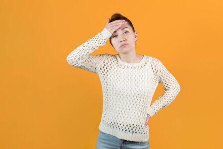 a sickly-looking girl clings to her head. A girl with a sore head is waiting for help and looks hopefully at the camera. Isolated on yellow background