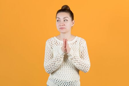 The young girl cunningly looks away, rubbing her hands. Isolated on a yellow background Stock fotó