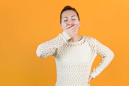 young girl yawns covering her mouth with one hand. Isolated on orange-yellow background Stock fotó