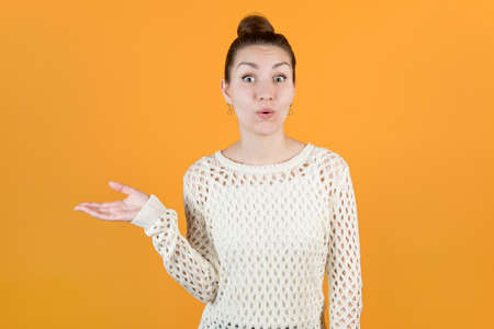girl holds out his hand to the side, taking something and expresses pleasant surprise. Isolated on orange-yellow background