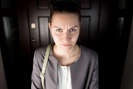 A stern young woman looks strictly while standing near the front door of a house inside