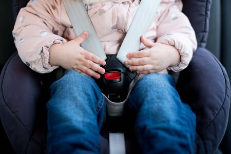 Hands of a little girl lie on the seat belt buckle of a child seat. Close-up Stock fotó