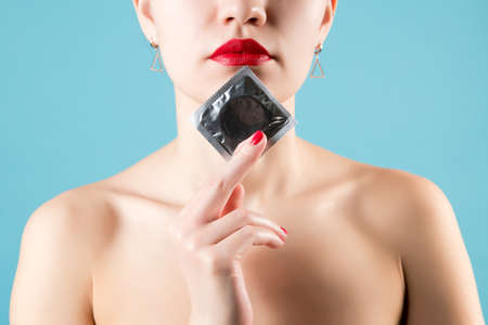 The girl holds a condom near her face. Close-up Stock fotó