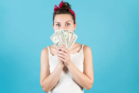 A young woman peeks out for the dollars she holds in front of her on a blue background