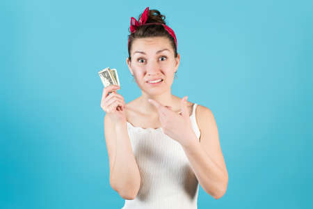 The girl indignantly points to a crumpled dollar in her hand on a blue background. isolated on blue Stock fotó