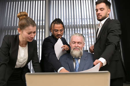 Colleagues amicably and actively discuss matters in the office of their manager. A gray-haired and respectable man listens to the opinions of his subordinates and discusses cases