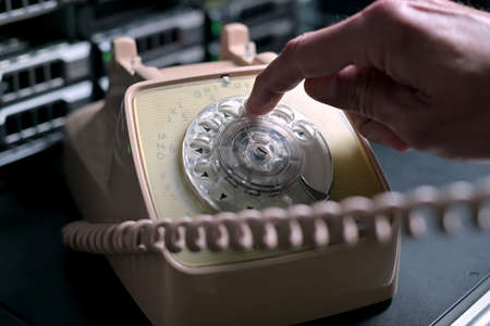 A man puts an old rotary telephone on a shelf against the backdrop of a modern server cabinet and starts dialing a phone number. Clash of eras, progress and technology