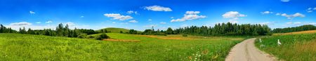 Beautiful panoramic landscape with the dark blue, cloudy, solar sky Standard-Bild
