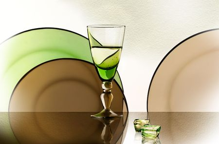 A glass beside a stack of white plates - on white background  photo