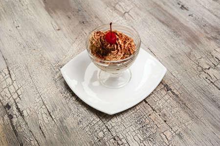 crumb: Ice cream with chocolate crumb and cherry on white plate