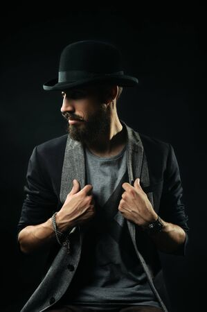 lapels: The brutal bearded man in a black bowler hat holding his lapels and looking away