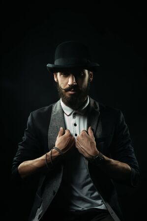 lapels: The brutal bearded man in a black bowler hat holding his lapels