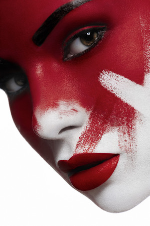 lips: Beautiful female model with white skin, red lips and blood on face. Halloween makeup.