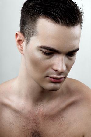 perspiring: Perspiring fashion male model looking down Stock Photo