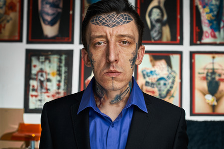 jacked: Closeup portrait of tattoo master in black jacked and blue shirt