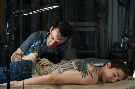 Tattoo artist makes a tattoo on the back of a young guy Stock Photo