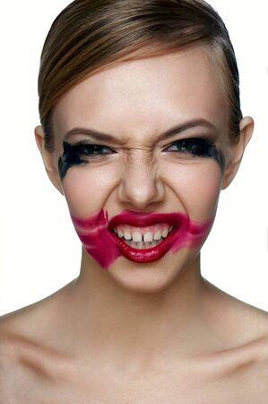 evil girl: Bellezza e salute pulita la pelle del male Ragazza con fumose Occhi e Labbra rosse con imbrattato Mascara e rossetto rosso su Smile spaventoso.