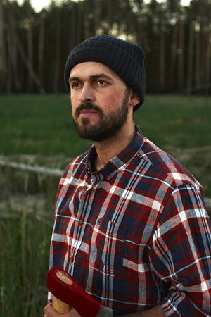 lumberjack shirt: Portrait of bearded Lumberjack with Axe in a Forest