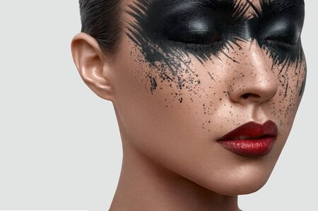 female magazine: Beauty female Model with closed eyes and black Paint Stains on her Face. Creative Face Art for Magazine or Poster Stock Photo