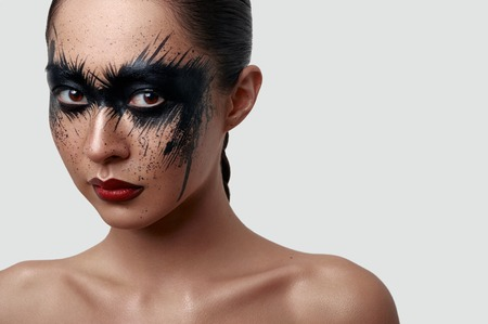 Beauty young Woman with Halloween creative Makeup. Black Paint Stains on her Skin