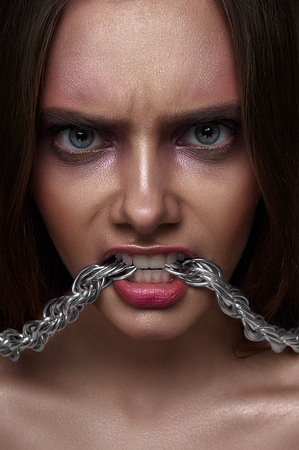 agressive: Fashion beauty young Woman with agressive Look and Chain in her Teeth