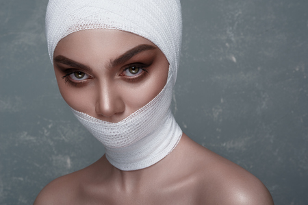 white bandage: Beauty Girl with big Eyes and white Bandage on her Head and Mouth