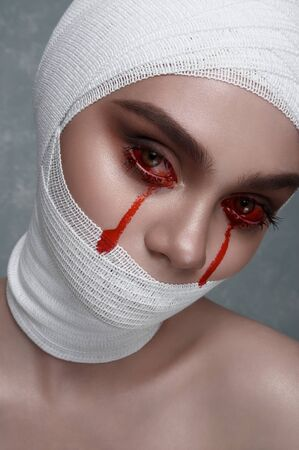 Beauty Woman with Halloween Makeup. Blood Drops from her Eyes and Bandage on Head Stock Photo