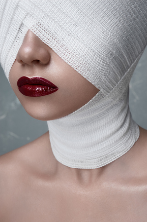 Fashion Beauty female Model with dark red Lips and Bandage on her Head. Halloween Makeup