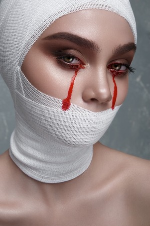 white bandage: Medical Horror. Young female Patient with Blood Drops from Eyes and white Bandage on Face. Halloween Makeup