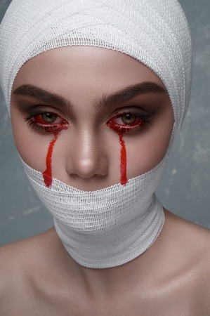 Halloween Makeup. Beauty female Patient with Blood Drops on Face