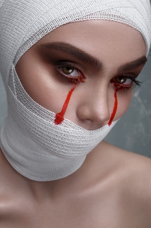 white bandage: Horror female Patient with Blood Drops from Eyes and white Bandage on Head and Mouth. Halloween Makeup Stock Photo