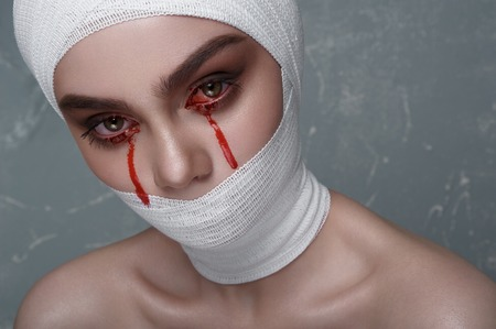 white bandage: Scary Girl with Blood from her Eyes and white Bandage on Head and Mouth. Halloween Makeup