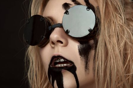 Young blonde Woman with Black Oil on her Face. Halloween Makeup Stock Photo