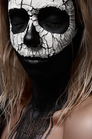 painted face: Halloween Makeup Ideas. White Skull on black painted Face of female Model