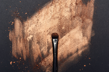 smeared: Make-up smeared on black Surface and beauty Brush Stock Photo