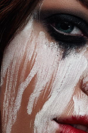 smeared: Woman with smeared White Paint on her Face Stock Photo