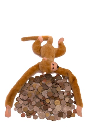 Pile of coins and a monkey isolated on white background