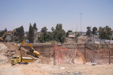 Two backhoes clearing a site after a building demolition.
