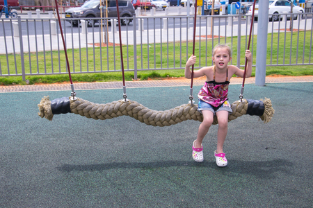 Beautiful girl play outdoor on swing Stock Photo